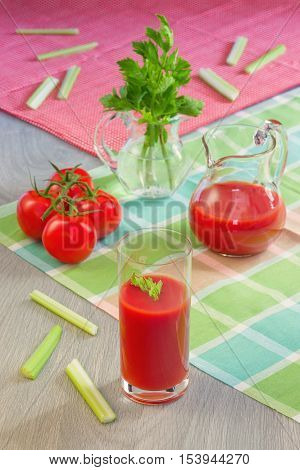 Glass with tomato juice, tomatoes, stalks and leaves of a celery on a table in style a rustic