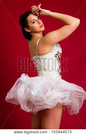 beautiful young girl in a white sexy dress on a red background