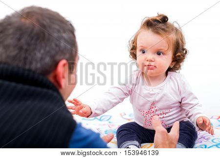 Adorable baby trying to grab her father hands