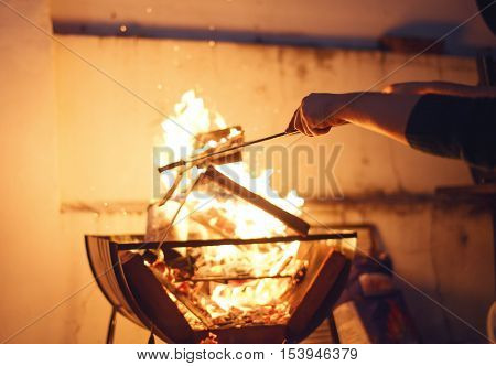 Man's arm doing the fire for grill at night