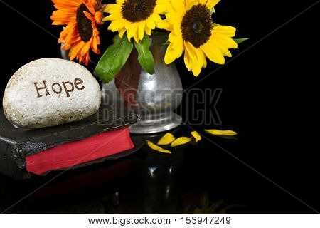 word hope carved in stone on Holy Bible with sunflower bouquet on black