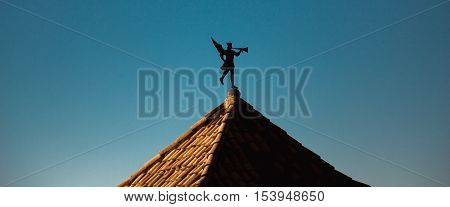 Weather vane in the form of a trumpeting angel on a tiled roof of an ancient building in Girona, blue clear sky in background