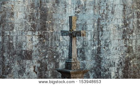 Tombstone in the form of a Catholic cross. Gray moss-covered stone. On the background of a stone wall, Girona, Spain