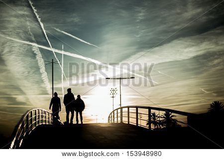 Three human silhouettes crossing the bridge. Backlight with beautiful evening sky with a lot of traces, Barcelona, Spain, vintage colour