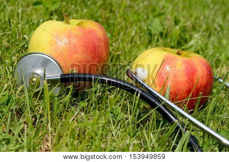 Two apples in the meadow connected to a stethoscope - health symbol
