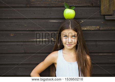 Young girl with a green apple on his head
