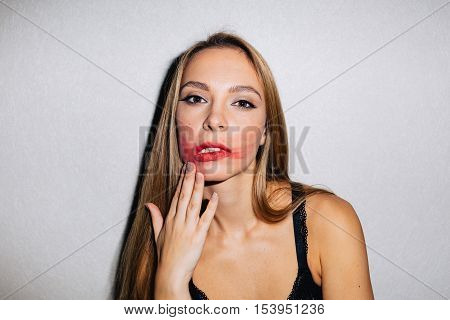 Studio shot of a female smudging her lipstick across her face