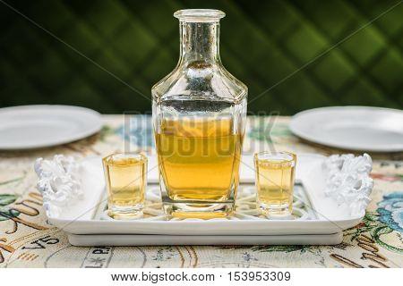 Carafe with honey vodka on white elegant tray