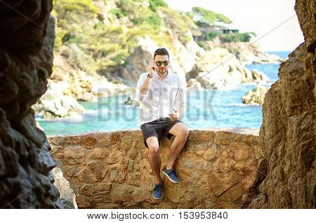 A handsome young man in the big cave view from inside. Beautiful sea and island view on the background.