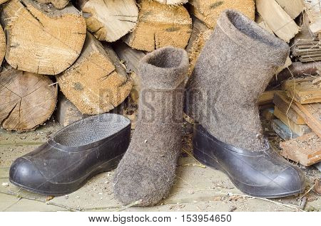 a pair of dirty old black rubber galoshes and boots grey wool sheepskin on the wooden floor next to the wood in the daytime