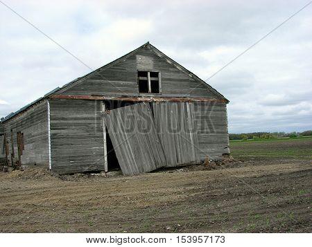 An abandoned farm building with a broken sliding door.