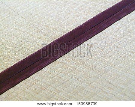 Tatami mat closeup with violet edging (heri). Straws visible.