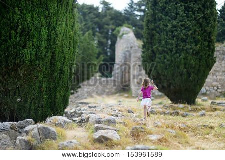 Little girl sightseeing historical ruins of Asclepieion poster