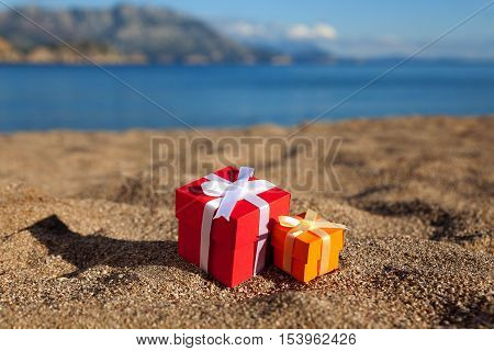 Group of red and orange gift boxes on a beach