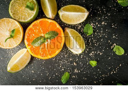 Fresh citrus fruits on a black slate table - tangerine, lime, lemon, mint leaves and brown cane sugar. Top view