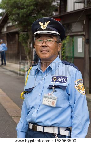 Kanazawa Japan - September 22 2016: Public officer is a security warden who directs traffic and parking in downtown Kanazawa. He is not a police officer but he keeps an eye on safety for all citizens in the neighborhood.