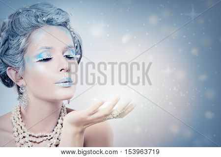 Winter Woman Fashion Model Blowing Snow at Night. Snow Queen Girl on Blue Background with Stars Snow and Glitters