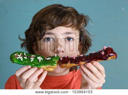 preteen handsome boy with eclair french dessert in hands