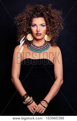 Beautiful Woman Fashion Model with Curly Hairstyle Makeup and Accessories in the Ethnic style