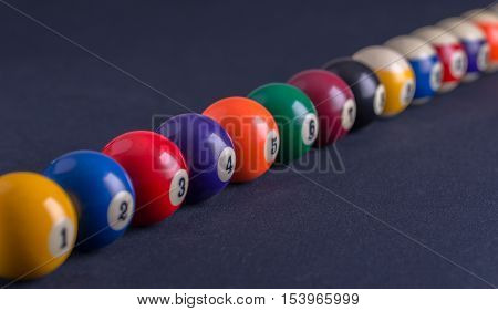Billiard balls in a row on blue table.