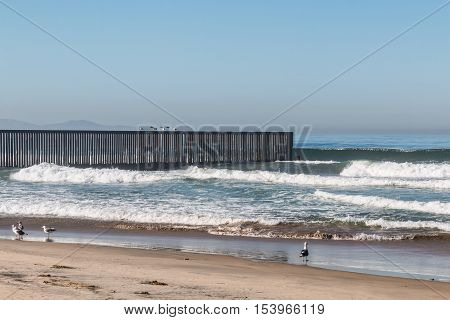 An empty beach at Border Field State Park, with the international border separating San Diego, California from Tijuana, Mexico in the background.