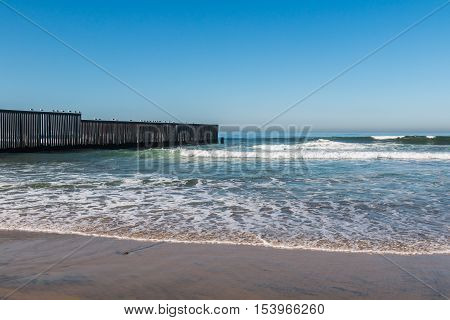 Waves on beach at Border Field State Park, with the international border separating San Diego, California from Tijuana, Mexico in the background.