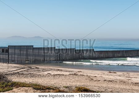 The international border wall separating Tijuana, Mexico from San Diego, California on the Border Field State Park beach with the Islas Los Coronados islands in the background.