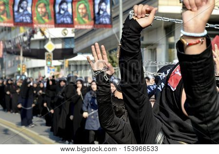 Istanbul Turkey - October 11 2016: Shiite Muslim women hold up their chained hands as they mourn during an Ashura procession. Turkish Shia Muslims mourning for Imam Hussain. Caferis take part in a mourning procession marking the day of Ashura in Istanbul
