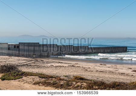 Border Field State Park beach with the international border fence between Tijuana, Mexico and San Diego, California, along with the Islas Los Coronados islands in the background.