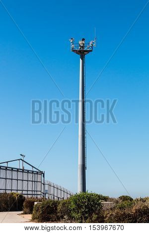 Border fence separating San Diego, California and Tijuana, Mexico, with a security tower with cameras and motion sensors on the US side.