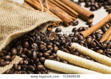 Coffee beans, burlap sack, cinnamon sticks and wafers on burlap surface. Selective focus
