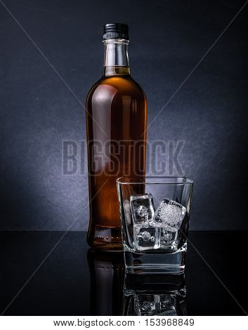 Whiskey With Ice Cubes In Glass Near Bottle On Black Background, Cold Atmosphere