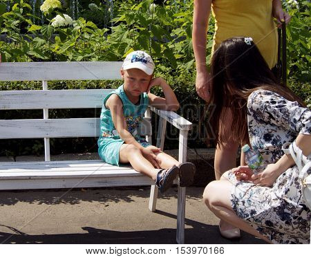 MOSCOW, RUSSIA - August 7, 2016: Frustrated elementary age boy sitting on a a park bench and mother sympathize with him. August 7, 2016 in Moscow, Russia