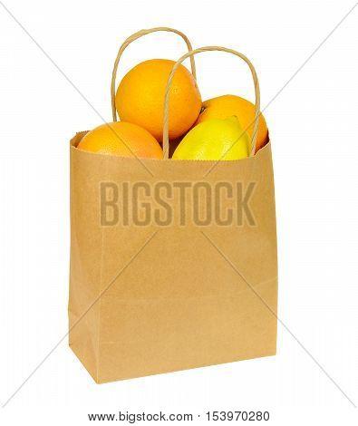Paper shopping bag full of citrus fruits isolated on white background. Ripe oranges, lemon and grapefruit.