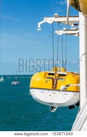 Yellow and White LIfeboat Suspended on Cables from Ship