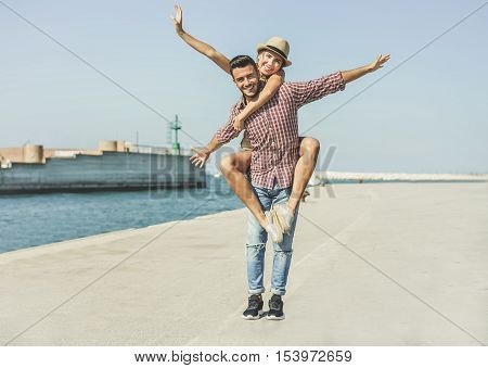Young cheerful man giving piggy back to his girlfriend on sea port - Smiling people having fun together outdoor for vacation in summer time - Love and youth concept - Vintage retro warm filter