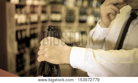 Sommelier uncorks a bottle of sparkling wine in a wine shop.