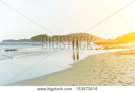 Silhouette of two children walking on water's edge holding buckets - Little girls playing on beach with amazing sunset in background - Vacation and family concept - Focus on people - Warm filter
