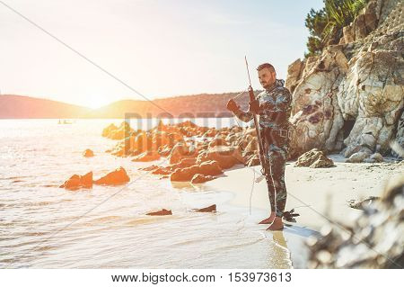 Young man preparing speargun for underwater fishing at sunset in italy - Male hunter getting ready for hunting wearing camouflage weatsuit - Extreme sport and hobby concept - Warm vintage filter