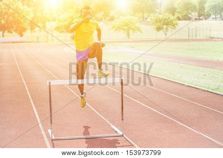 African athlete jumping hurdle in a athletic running track with back lighting - Young man training outdoor in stadium - Sport and healthy lifestyle concpt - Warm filter with soft focus on face