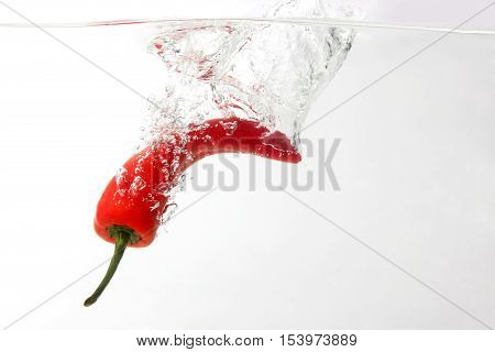 the red chili pepper falling in water