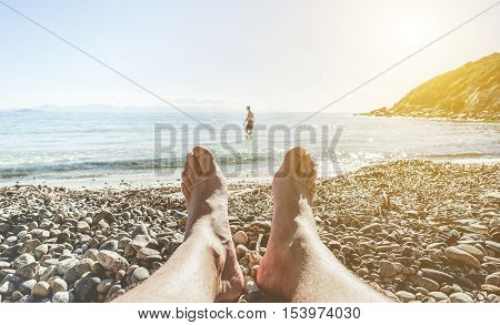Man's feet on little stones beach with person walking inside water in background - Young guy lying dow with sea view - Freedom lifestyle and vacation concept - Focus on feet - Warm filter