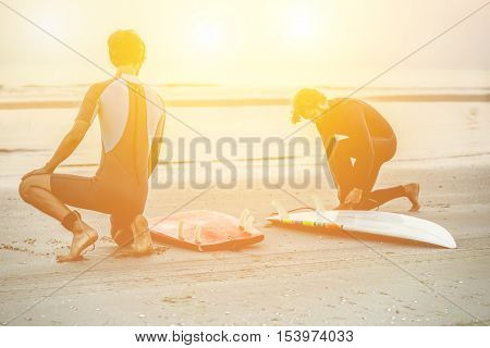 Two silhouette friends wearing swimwear with surfboards on beach with sunlight in background - Surfers preparing the boards and equipment for surfing - Extreme sport concept - Focus on left man