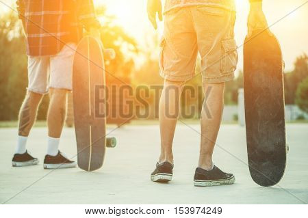 Skaters friends outdoor in urban city with skateboards in their hands - Young people training longboard extreme sport - Friendship concept - Warm filter