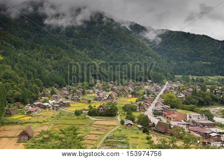 Shirakawago Japan - September 23 2016: Aerial view on the hamlet of Shirakawago shows the entire village with the central road cutting it in half. green forest and low hanging clouds. Yellow rice paddies add color.