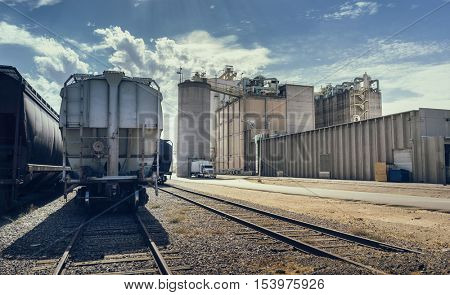 Desert landscape.  Arizona heat beats down on industrial building and rail road track with cargo containers, silo and large facility in distance.