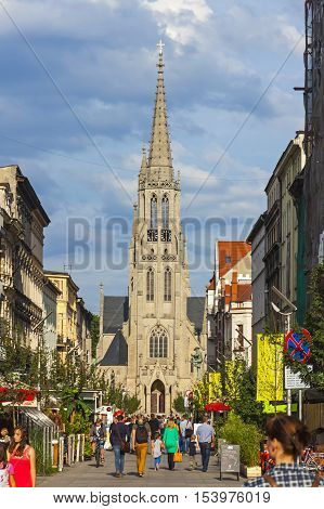 KATOWICE POLAND - JULY 28 2015: St. Mary's Street (Polish: Ulica Mariacka) popular place in Katowice attracted by its many pubs and restaurants. St. Mary's Church (Kosciol Mariacki) on the background