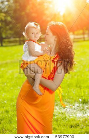 Beauty Mom and baby outdoors. Happy family playing in nature. Mom and kid. Mother and child.