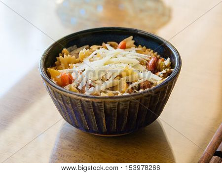 A bowl of minestrone soup with shredded fresh parmesan cheese