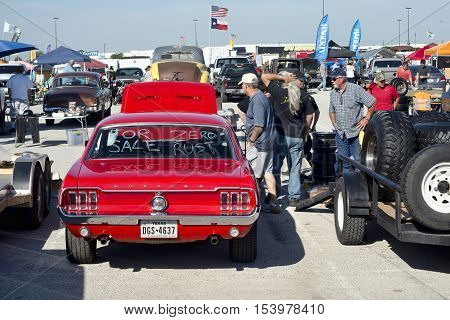 Grand Prairie Texas- Oct.29 2016 Cars for sale at local car swap meet. people looking at a 1966 red Ford Mustang.